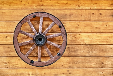 carreta madera: Una rueda de carreta antigua decorado con una pared de madera Foto de archivo