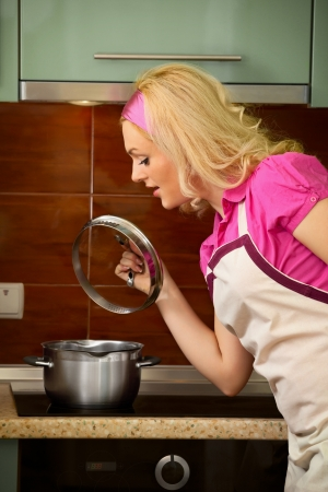 A young blonde girl prepares food on kitchen photo