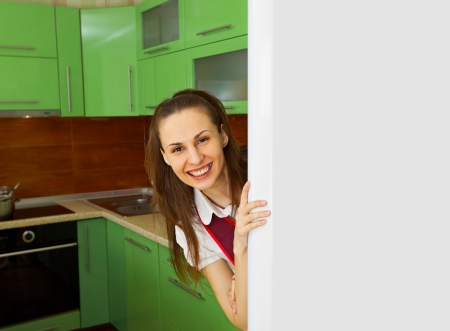 Young happy woman on kitchen near the refrigerator photo