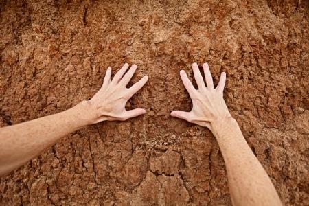tierra fertil: Las manos tocan el suelo de arcilla seca