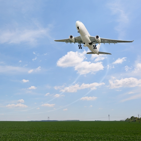 Passenger aircraft taking off over the fields photo