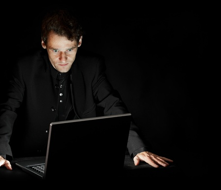 thinks: Portrait of hacker with laptop on dark background Stock Photo