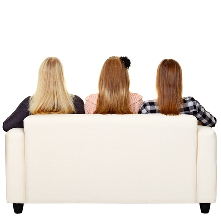 Young women sitting on sofa - rear view. Isolated on white Standard-Bild