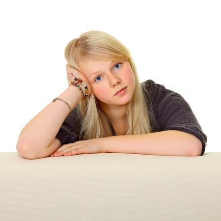 Das junge Mädchen lehnt sich auf der Rückseite des Sofas