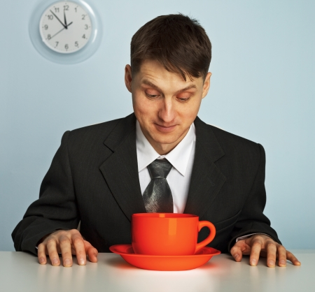Businessman going to drink a very strong and very hot coffee photo