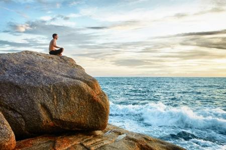Ein Mann macht Yoga an der Küste - Meditation Standard-Bild
