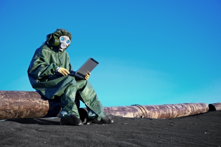 A scientist working with a laptop on a chemically contaminated area photo