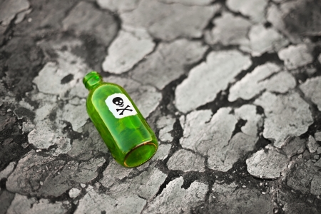 Bottle with the poison lying on poisoned ground 写真素材