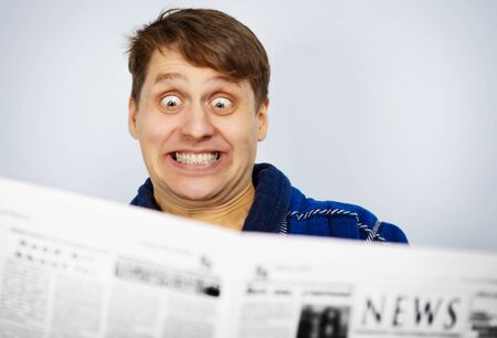 Man shocked while reading the news from newspapers Stock Photo - 14547894