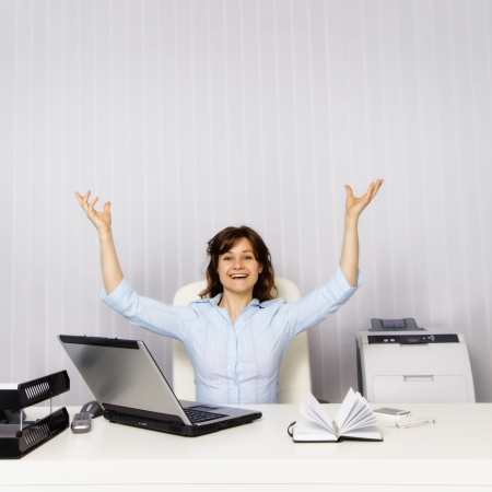 Happy young woman in the office workplace photo