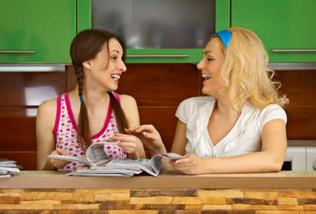 Two girlfriends in the kitchen leaf through magazines photo