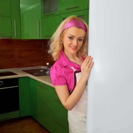 Housewife in the kitchen near the refrigerator photo