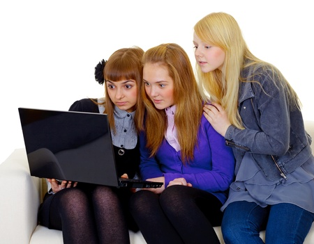 Concerned teenager girls with a black laptop isolated on white background Stock Photo - 14830785