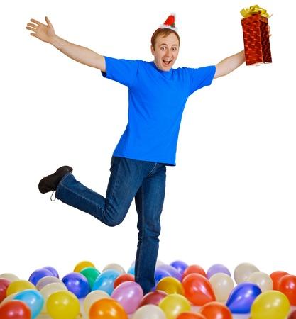 A happy man with a Christmas gift dancing among balls photo