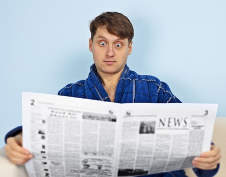 emotionality: A man reads a newspaper with a amazement