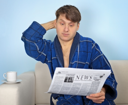 emotionality: Person reads a newspaper with pensiveness on blue background Stock Photo