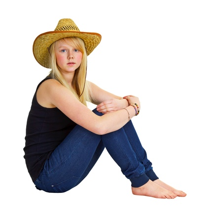 A young girl in a farmer dress sitting isolated on white background photo