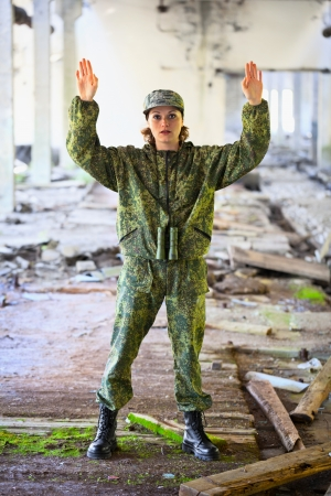 female soldier: Young woman in military uniform surrenders Stock Photo