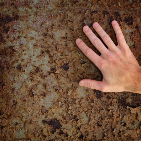 color skin brown: Hand touches the old rusty metal surface Stock Photo