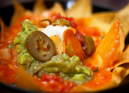 Nachos with salsa verde and olives close up photo