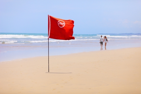 Tropical beach and a red flag. Swimming is forbidden! photo