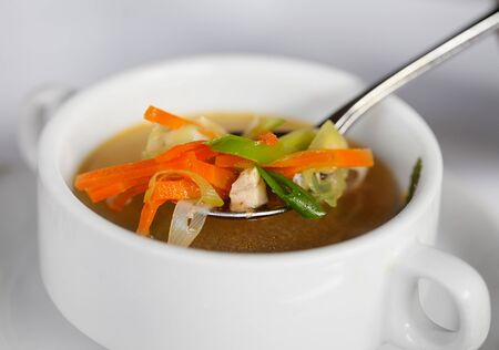 chiken: Chicken soup with vegetables in spoon and white deep plate