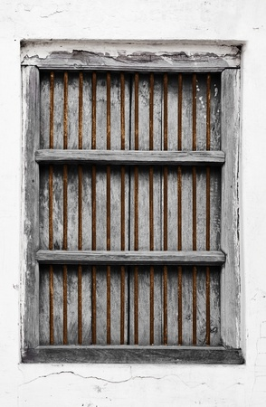 Old wooden grunge window with rusty grate photo