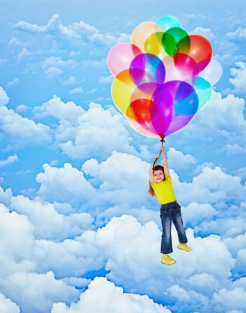 Cheerful child flies with balloons on the sky background photo