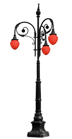Vintage cast iron lamppost with red light isolated on white background photo