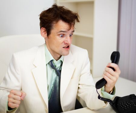 Very angry business man in white office with telephone handset Stock Photo - 18063619