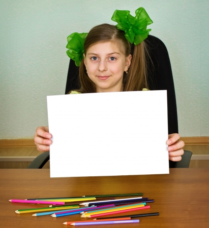 Schoolgirl artist with green bows shows white blank paper sheet under table with color pencils photo