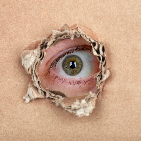 Curious espionage eye in hole in brown carton wall photo
