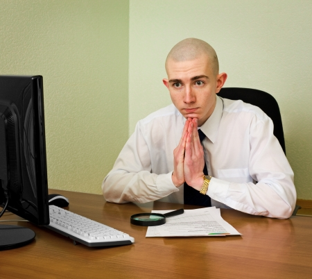 Thoughtful puzzle office manager sits at table with documents and computer photo