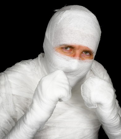 Completely bandaged man is ready to fight with clenched fists on black background photo