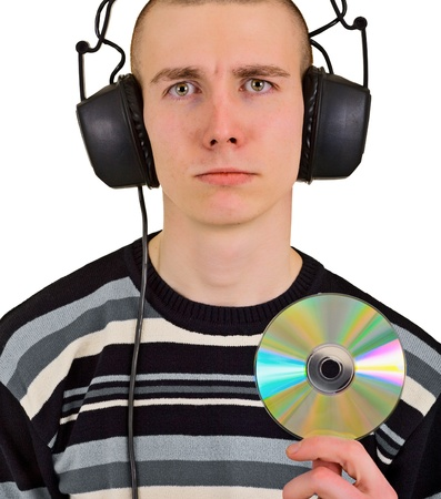 Sad disappointed teenager male music lover with big headphones and compact disk photo