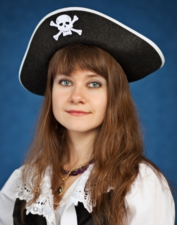 pirate girl: Young woman in pirate hat on blue background Stock Photo