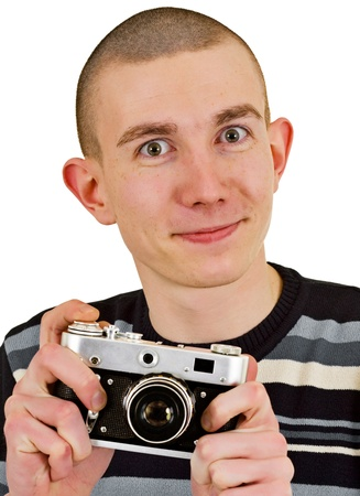 smug: Satisfied young man carried away with small vintage camera