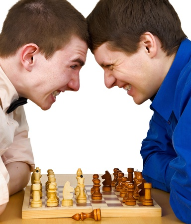 Two aggressive chess opponents fights with his forehead under chess board photo