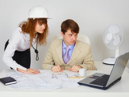 Business construction industry team with engineering drawing looking on laptop in white office photo