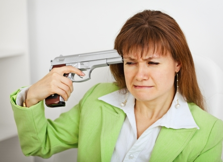 Upset business woman in green suit keeps gun near his temple on white office background photo