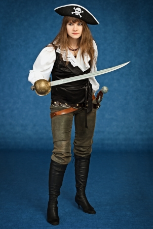 Young woman in pirate suit with sabre on blue background photo