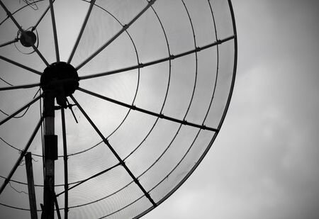 telecommunication equipment: An old rusty parabolic antenna on sky background