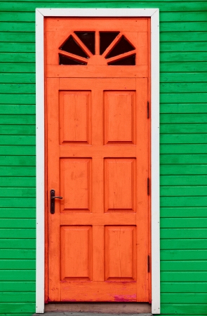 view of a wooden doorway: Red vintage wooden door on green rustic wall