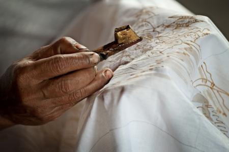 kelet ázsiai kultúra: Batikolás egy fehér ruhával folyamatot közelről. Indonézia Stock fotó