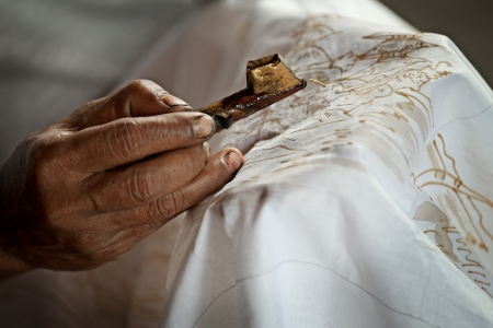 Batik painting on a white cloth process close up. Indonesia