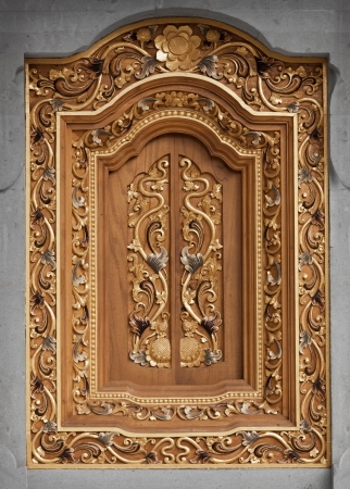 wood carving door: Richly decorated vintage wooden window in the wall of the temple. Indonesia. Stock Photo