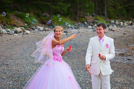 Bride and groom having fun with soap bubbles outdoors photo