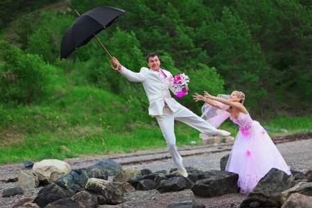 Groom with umbrella wind blows from the bride - wedding joke Stock Photo