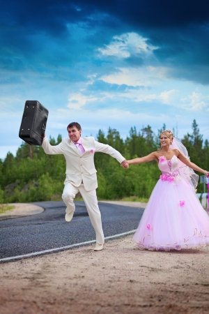 Groom with a suitcase seeks a way for a honeymoon photo