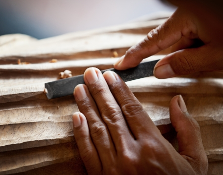 chisel: Hands woodcarver with the tool close up